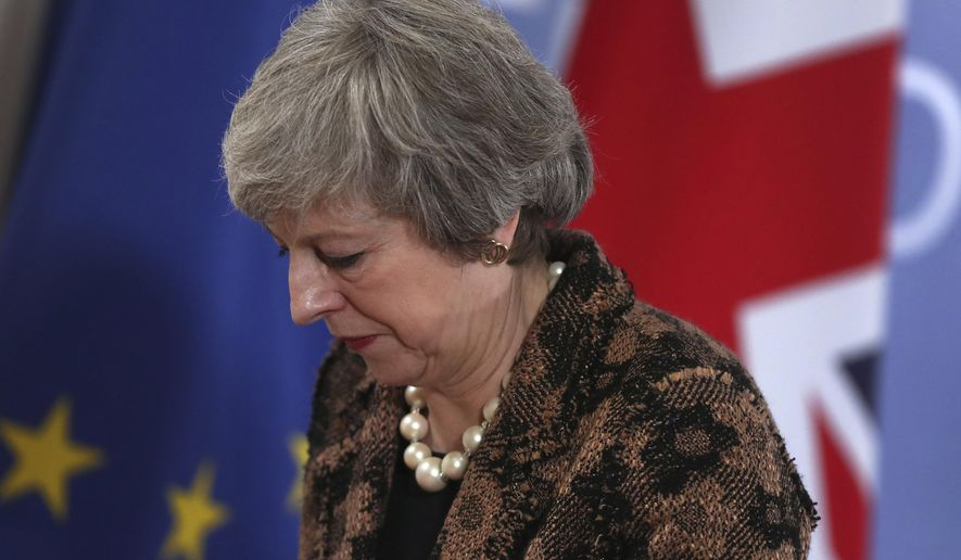 British Prime Minister Theresa May walks by the Union flag and the EU flag as she departs a media conference at an EU summit in Brussels, Friday, Dec. 14, 2018. European Union leaders expressed deep doubts Friday that British Prime Minister Theresa May can live up to her side of their Brexit agreement and they vowed to step up preparations for a potentially-catastrophic no-deal scenario. (AP Photo/Francisco Seco)