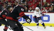 Washington Capitals' Alex Ovechkin (8), of Russia, shoots and scores while Carolina Hurricanes' Calvin de Haan (44) and Justin Faulk (27) defend at left during the first period of an NHL hockey game in Raleigh, N.C., Friday, Dec. 14, 2018. (AP Photo/Gerry Broome)