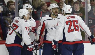 Washington Capitals' Alex Ovechkin (8), of Russia, celebrates his goal against the Carolina Hurricanes with T.J. Oshie (77), Nic Dowd (26) and Jonas Siegenthaler, of the Czech Republic, during the second period of an NHL hockey game in Raleigh, N.C., Friday, Dec. 14, 2018. (AP Photo/Gerry Broome)