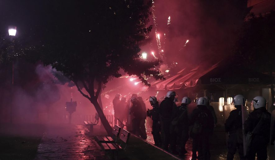 Riot police take cover as protesters throw fireworks during a rally in the northern Greek city of Thessaloniki, Friday, Dec. 14, 2018. Hundreds of people protest against government efforts to end a three-decade-old dispute with neighboring Macedonia as the Greek Prime Minister Alexis Tsipras delivered a speech to party cadres and supporters. (AP Photo/Giannis Papanikos)