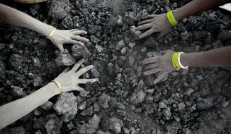 FILE - In this Monday, Dec. 14, 2015, file photo, Indian women use bare hands to pick reusable pieces from heaps of used coal discarded by a carbon factory in Gauhati, India. Thirteen young miners were missing and feared dead following the collapse of a shaft and flooding of a coal mine they were digging illegally in India's remote northeast, police said Friday, Dec. 14, 2018. (AP Photo/ Anupam Nath, File)