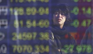 A woman is reflected on the electronic board of a securities firm in Tokyo, Friday, Dec. 14, 2018. Asian markets tumbled on Friday after China reported weaker-than-expected economic data, stirring up worries about the state of the world's second largest economy. (AP Photo/Koji Sasahara)