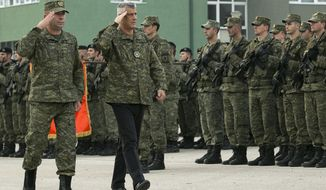 Kosovo president Hashim Thaci, center, flanked by KSF Commander Rrahman Rama as they inspect members of Kosovo Security Force in capital Pristina, Kosovo, on Thursday, Dec. 13, 2018. Kosovo lawmakers are set to transform the Kosovo Security Force into a regular army, a move that significantly heightened tension with neighboring Serbia. (AP Photo/Visar Kryeziu)