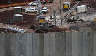 In this Thursday, Dec. 13, 2018 photo, Israeli military equipment works at the Lebanese-Israeli border next to a wall that was built by Israel in the southern village of Kafr Kila, Lebanon. As Israeli excavators dig into the rocky ground, Lebanese across the frontier gather curiously to watch in real time what Israel calls the Northern Shield operation aimed at destroying attack tunnels built by Hezbollah. But Lebanese soldiers in new camouflaged posts, behind sandbags, or inside abandoned homes underscore the real anxiety that any misstep could lead to a conflagration between the two enemy states that no one seems to want. (AP Photo/Hussein Malla)