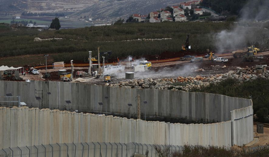 In this Thursday, Dec. 13, 2018 photo, Israeli military equipment works on the Lebanese-Israeli border, next to a wall that was built by Israel, in the southern village of Kafr Kila, Lebanon. As Israeli excavators dig into the rocky ground, Lebanese across the frontier gather to watch what Israel calls the Northern Shield operation aimed at destroying attack tunnels built by Hezbollah. But Lebanese soldiers in new camouflaged posts, behind sandbags, or inside abandoned homes underscore the real anxiety that any misstep could lead to a conflagration between the two enemy states that no one seems to want. (AP Photo/Hussein Malla)