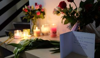 Tributes are placed on a table in an apartment block in Rotterdam, Netherlands, on Friday Dec. 14, 2018, where American student Sarah Papenheim lived. Papenheim, a 21-year-old psychology student at Erasmus University, was fatally stabbed at her home on Wednesday. Police say a 23-year-old man has been arrested on suspicion of involvement in her death. (AP Photo/Mike Corder)