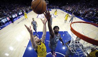 Indiana Pacers' Domantas Sabonis (11) and Philadelphia 76ers' Joel Embiid (21) leap for a rebound during the second half of an NBA basketball game, Friday, Dec. 14, 2018, in Philadelphia. Indiana won 113-101. (AP Photo/Matt Slocum)