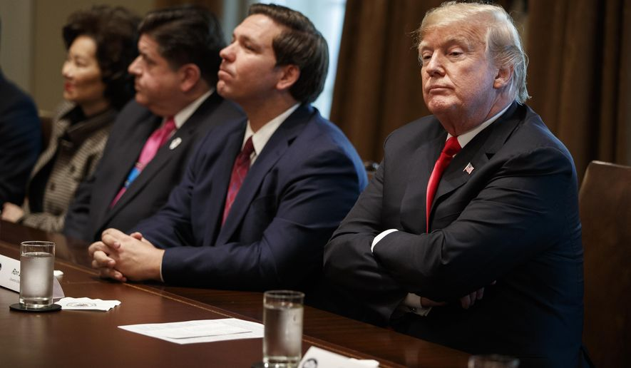 President Donald Trump listens to a question from a reporter during a meeting with newly elected governors in the Cabinet Room of the White House, Thursday, Dec. 13, 2018, in Washington. From left, Secretary of Transportation Elaine Chao, Governor-elect J.B. Pritzker, D-Ill., Governor-elect Ron DeSantis, R-Fla., and Trump. (AP Photo/Evan Vucci)