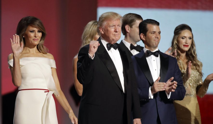 In this Jan. 20, 2017, file photo President Donald Trump, center, raises his fist alongside first lady Melania Trump, left, and eldest son Donald Trump, Jr., after dancing at the Liberty Ball following his inauguration in Washington. (AP Photo/Patrick Semansky)