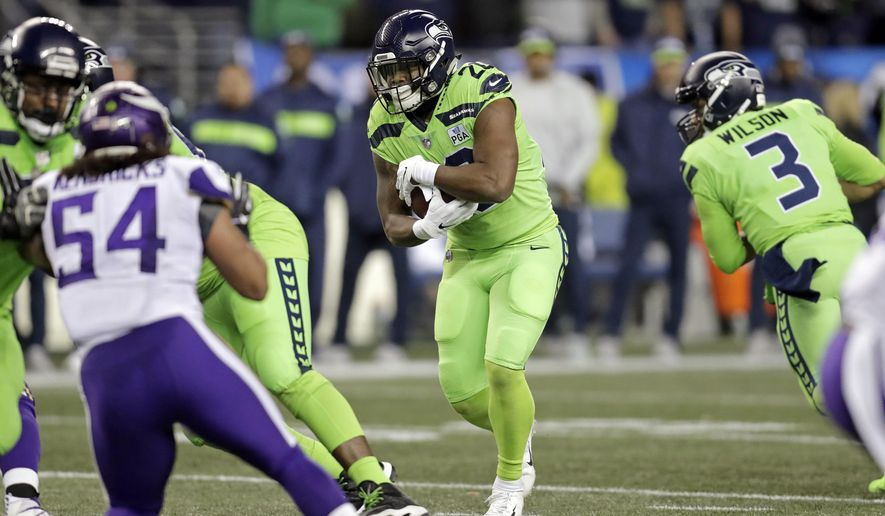 Seattle Seahawks' Rashaad Penny, center, carries against the Minnesota Vikings in the first half of an NFL football game, Monday, Dec. 10, 2018, in Seattle. (AP Photo/Stephen Brashear)