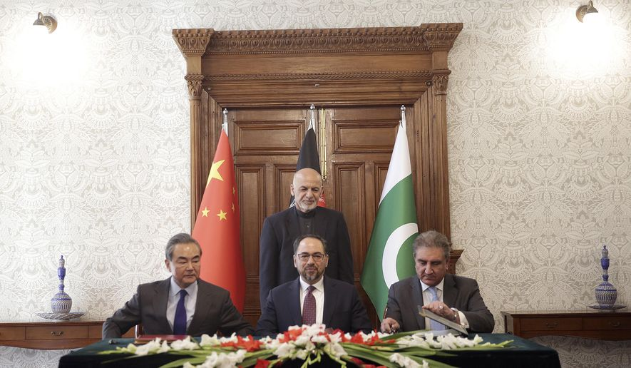 Afghanistan's President Ashraf Ghani, standing, watches as Afghanistan's Minister of Foreign Affairs Salahuddin Rabbani, center, Pakistan's Foreign Minister Shah Mehmood Qureshi, right, and Chinese Foreign Minister Wang Yi, left, sign the agreement during a meeting at the presidential palace in Kabul, Afghanistan, Saturday, Dec. 15, 2018. Afghanistan, Pakistan, and China are meeting in the Afghan capital to discuss trade, development and ending the region's relentless conflicts. (AP Photo/Massoud Hossaini)