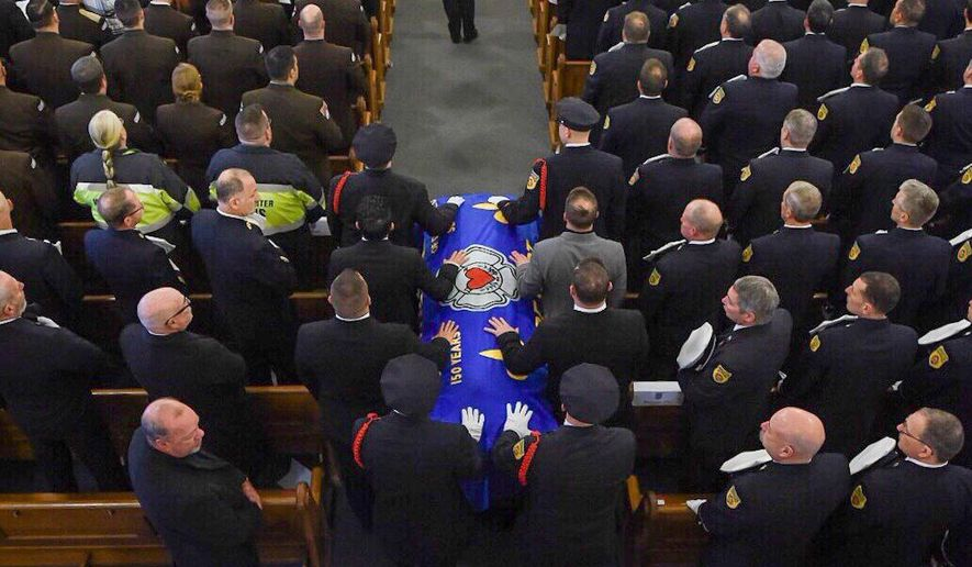 The casket with Worcester firefighter Christopher Roy is brought into St. John Church for his funeral mass Saturday, Dec. 15, 2018 in Worcester, Mass.  Roy was hurt in the pre-dawn fire last Sunday, and was taken to the hospital where he was pronounced dead. The Shrewsbury resident was a single father who leaves behind a 9-year-old daughter as well as his parents and other relatives. (Ashley Green/Worcester Telegram & Gazette via AP)