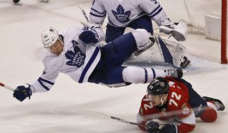 Toronto Maple Leafs defenseman Morgan Rielly, left, flips over Florida Panthers center Frank Vatrano during the second period of an NHL hockey game on Saturday, Dec. 15, 2018, in Sunrise, Fla. (AP Photo/Brynn Anderson)