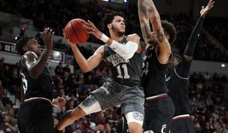 Mississippi State guard Quinndary Weatherspoon (11) looks for a teammate to pass to while Cincinnati defenders cover him during the first half of an NCAA college basketball game in Starkville, Miss., Saturday, Dec.15, 2018. (AP Photo/Rogelio V. Solis)