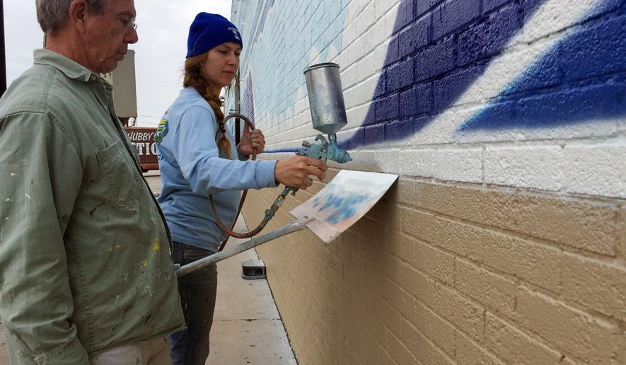 In this Wednesday, Dec. 5, 2018 photo, artists John Olvey and Kaleigh Glover paint a mural on the side of the Corpus Christi Trade Center on in Corpus Christi, Texas.  The pair spent eight days working on the 200-foot (61-meter) outdoor artwork, which features beach scenery with crashing waves and palm trees.(Mark Young/Corpus Christi Caller-Times via AP)