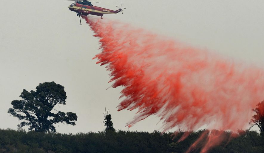 "FILE - In this Aug. 13, 2016 file photo, a fire attack helicopter makes a retardant drop during a firing operation on the ridge between Mount Manuel and the Coast Ridge Road while fighting the Soberanes Fire near the village of Big Sur, Calif. The so-called Soberanes Fire burned its way into the record books as the most expensive wildland firefight in U.S. history in what a new report calls ""an extreme example of excessive, unaccountable, budget-busting suppression spending that is causing a fiscal crisis in the U.S. Forest Service."" (David Royal/The Monterey County Herald via AP, File)"