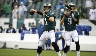 FILE - In this Sept. 23, 2018, file photo, Philadelphia Eagles quarterback Carson Wentz (11) and quarterback Nick Foles (9) throw before an NFL football game against the Indianapolis Colts, in Philadelphia. Wentz's back injury will sideline him for Sunday, Dec. 16 game at the Los Angeles Rams. With the Eagles' No. 1 quarterback out, Nick Foles gets another opportunity to rescue the team he led to a Super Bowl victory last season.  (AP Photo/Matt Rourke, File) **FiLE**