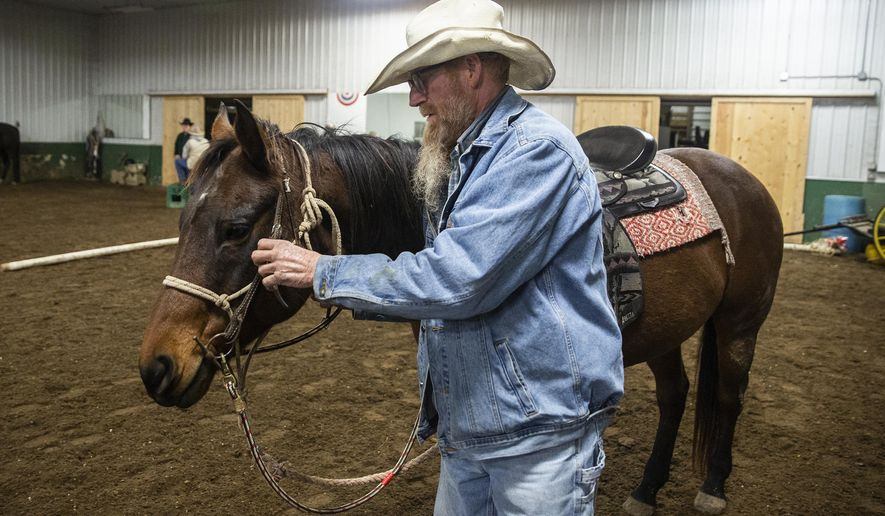 """In this Thursday, Nov. 15, 2018 photo, Carroll """"Hippie"""" Waser, a Marine veteran, spends time with Danny, one of the horses at Wildwood Hills Ranch of Iowa near St. Charles, Iowa. (Kelsey Kremer/The Des Moines Register via AP)"""