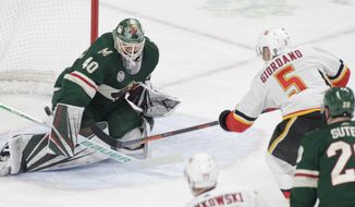 Calgary Flames defenseman Mark Giordano (5) scores a short-handed goal against Minnesota Wild goaltender Devan Dubnyk (40) during the first period of an NHL hockey game Saturday, Dec. 15, 2018, in St. Paul, Minn. Minnesota Wild defenseman Ryan Suter (20) looks on. (AP Photo/Paul Battaglia)