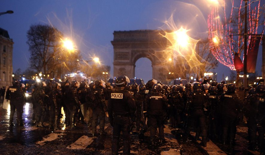 Police forces secure the Champs-Elysees avenue, Saturday, Dec. 15, 2018 in Paris. The demonstrations against France's high cost of living _ sapped by cold weather, rain and recent concessions by French President Emmanuel Macron _ were significantly smaller Saturday than at previous rallies. (AP Photo/Kamil Zihnioglu)