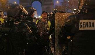 """A demonstrator holds a flower in front of riot police officers Saturday, Dec. 15, 2018 in Paris. Tear gas billowed Saturday across the French capital's protest-scarred Champs-Elysees after a day of largely peaceful demonstrations and water cannons shot into the crowds on the fifth straight weekend of protests by the country's """"yellow vest"""" movement. (AP Photo/Michel Euler)"""