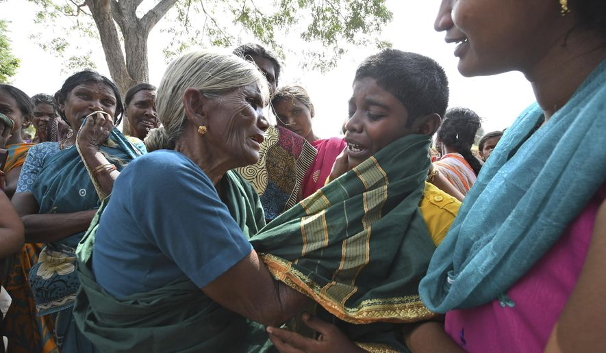 A boy cries consoled by his grandmother after his mother died of food poisoning at Bidarahalli, near Sulawadi village in Chamarajnagar district of Karnataka state, India, Saturday, Dec. 15, 2018. Police on Saturday arrested three people after at least 10 died of suspected food poisoning following a ceremony to celebrate the construction of a new Hindu temple in southern India. (AP Photo/Madhusudhan Sr)