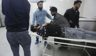 Kashmiri men wheel in an injured civilian on a stretcher inside a hospital in Srinagar, Indian controlled Kashmir, Saturday, Dec. 15, 2018. At least seven civilians were killed and nearly two dozens injured when government forces fired at anti-India protesters in disputed Kashmir following a gunbattle that left three rebels and a soldier dead on Saturday, police and residents said. (AP Photo/Mukhtar Khan)