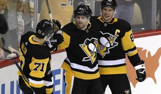 Pittsburgh Penguins' Phil Kessel (81) celebrates his winning goal with Sidney Crosby (87) and Evgeni Malkin (71) in the overtime period of an NHL hockey game against the Los Angeles Kings in Pittsburgh, Saturday, Dec. 15, 2018. (AP Photo/Gene J. Puskar)