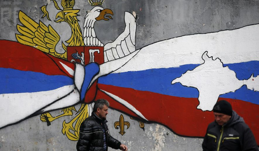 People walk by the graffiti that shows Serbian, left, and Russian flags with maps of Kosovo and Crimea in northern, Serb-dominated part of ethnically divided town of Mitrovica, Kosovo, Saturday, Dec. 15, 2018. Serbia threatened a possible armed intervention in Kosovo after the Kosovo parliament on Friday overwhelmingly approved the formation of a regular army, and Russia denounced the move. (AP Photo/Darko Vojinovic)