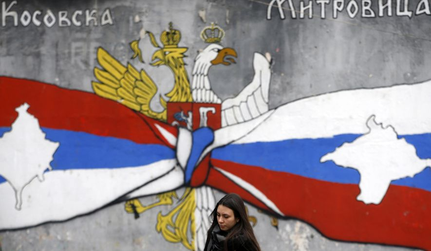 """A woman walks by graffiti showing the Serbian flag, left, and Russian flags with maps of Kosovo and Crimea in northern, Serb-dominated part of ethnically divided town of Mitrovica, Kosovo, Saturday, Dec. 15, 2018. Serbia threatened a possible armed intervention in Kosovo after the Kosovo parliament on Friday overwhelmingly approved the formation of an army. Russia denounced the move to form a Kosovo army, saying the ethnic Albanian force must be """"disbanded"""" by NATO in Kosovo. (AP Photo/Darko Vojinovic)"""