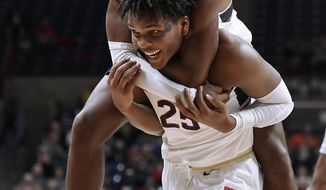 Connecticut's Christian Vital, top, jumps onto the back of Connecticut's Josh Carlton at the end of the first half of an NCAA college basketball game against Manhattan, Saturday, Dec. 15, 2018, in Storrs, Conn. (AP Photo/Jessica Hill)