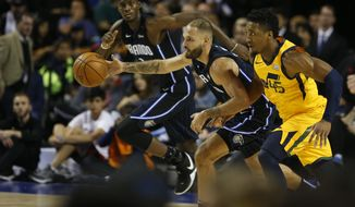 Orlando Magic's Evan Fournier, center, controls a ball as Utah Jazz's Donovan Mitchell tries to steal in a regular-season NBA basketball game in Mexico City, Saturday Dec. 15, 2018. (AP Photo/Claudio Cruz)