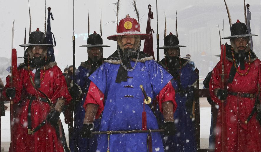 Palace guards wearing traditional military uniforms stand during snowfall at the landmark Gyeongbok Palace, the main royal palace during the Joseon Dynasty, in Seoul, South Korea, Thursday, Dec. 13, 2018. (AP Photo/Ahn Young-joon)