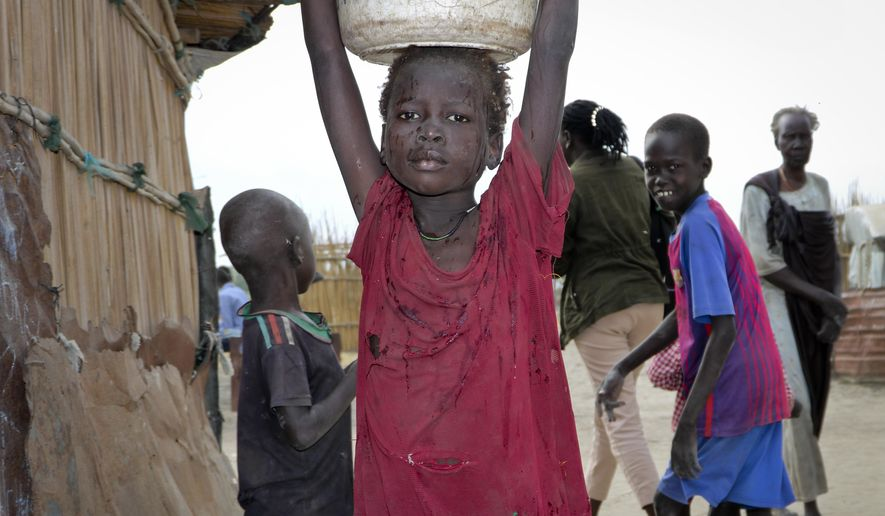 In this photo taken Sunday, Dec. 9, 2018, a young girl carries water on her head in Koythiey displaced person's camp on the outskirts of Bentiu town in South Sudan. Six months ago planning ahead in civil war-torn South Sudan seemed impossible but now, after warring sides signed a new peace deal in September that the government vows will hold, some are starting to rebuild their lives. (AP Photo/Sam Mednick)