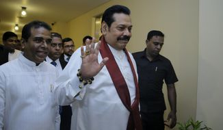 FILE - In this Nov. 29,2018, file photo, Sri Lanka's disputed Prime Minister Mahinda Rajapaksa, gestures as he arrives for a meeting with his supporting lawmakers at the parliamentary complex in Colombo, Sri Lanka. A Sri Lankan lawmaker said that the disputed Prime Minister Rajapaksa will resign Saturday to end the country's political crisis. (AP Photo/Eranga Jayawardena, File)