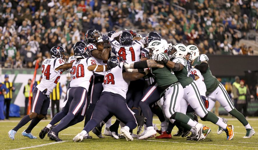 A scrum is formed on the goalie as New York Jets running back Elijah McGuire (25) scores a touchdown run against the Houston Texans during the second half of an NFL football game, Saturday, Dec. 15, 2018, in East Rutherford, N.J. (AP Photo/Adam Hunger)