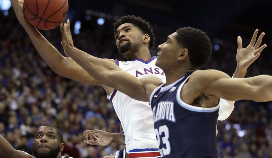 Kansas forward Dedric Lawson, center, rebounds against Villanova forward Jermaine Samuels, right, during the first half of an NCAA college basketball game in Lawrence, Kan., Saturday, Dec. 15, 2018. (AP Photo/Orlin Wagner)