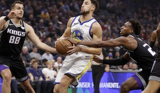 Golden State Warriors guard Klay Thompson, center, drives to the basket between Sacramento Kings' Nemanja Bjelica, left, and Buddy Hield, right, during the first half of an NBA basketball game Friday, Dec. 14, 2018, in Sacramento, Calif. (AP Photo/Rich Pedroncelli)