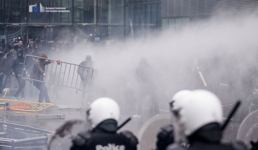 Protestors face off against the police during an anti-migrant demonstration outside of EU headquarters in Brussels, Sunday, Dec. 16, 2018. Police used tear gas and water cannons to disperse demonstrators around the European Union headquarters at the end of a march to protest the adoption of a U.N. migration pact. (AP Photo)