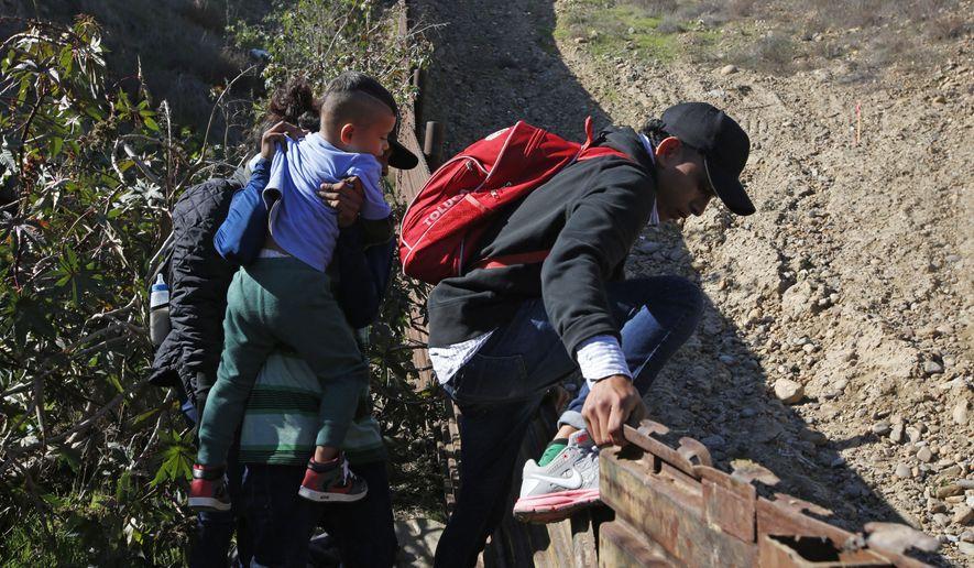 Honduran migrants cross the U.S. border wall to San Diego, California from Tijuana, Mexico, Sunday, Dec. 16, 2018, before turning themselves in to U.S. border patrol agents. (AP Photo/Moises Castillo)