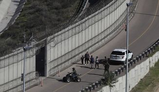 Honduran asylum seekers are taken into custody by U.S. Border Patrol agents after the group crossed the U.S. border wall into San Diego, California, seen from Tijuana, Mexico, Sunday, Dec. 16, 2018. (AP Photo/Moises Castillo)