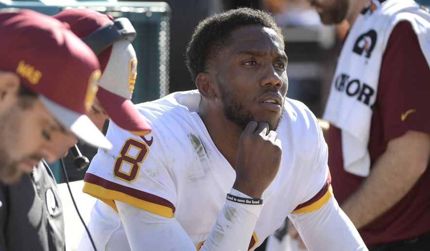 Washington Redskins quarterback Josh Johnson (8) watches play as he takes a break on the bench during the first half of an NFL football game against the Jacksonville Jaguars, Sunday, Dec. 16, 2018, in Jacksonville, Fla. (AP Photo/Phelan M. Ebenhack) **FILE**