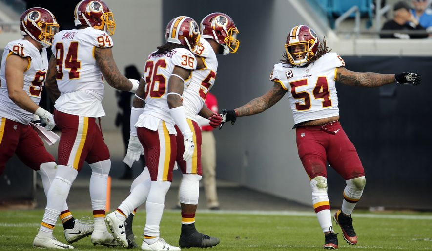 Washington Redskins players including Mason Foster (54), free safety D.J. Swearinger (36), outside linebacker Preston Smith (94) and outside linebacker Ryan Kerrigan (91) celebrate a defensive play against the Jacksonville Jaguars during the first half of an NFL football game, Sunday, Dec. 16, 2018, in Jacksonville, Fla. (AP Photo/Stephen B. Morton)