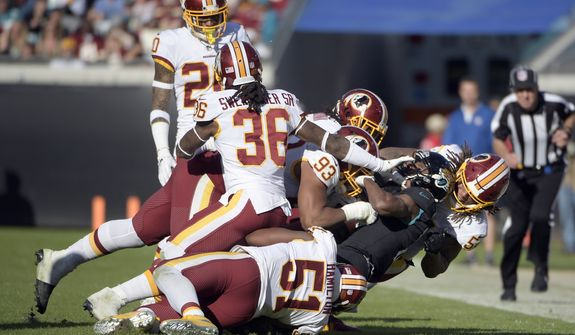 Jacksonville Jaguars wide receiver Dede Westbrook, second from right, is stopped by the Washington Redskins defense including linebacker Shaun Dion Hamilton (51), free safety D.J. Swearinger (36), strong safety Ha Ha Clinton-Dix (20) and defensive end Jonathan Allen (93) during the second half of an NFL football game, Sunday, Dec. 16, 2018, in Jacksonville, Fla. (AP Photo/Phelan M. Ebenhack)