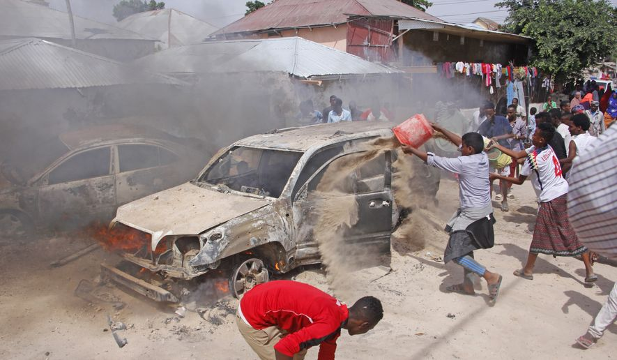 Somalis pour sand to smother a car fire after a car bomb in Mogadishu, Somalia, Sunday, Dec. 16, 2018. At least one person was killed and others injured Sunday and nobody has claimed responsibility for the blast. (AP Photo/Farah Warsameh)