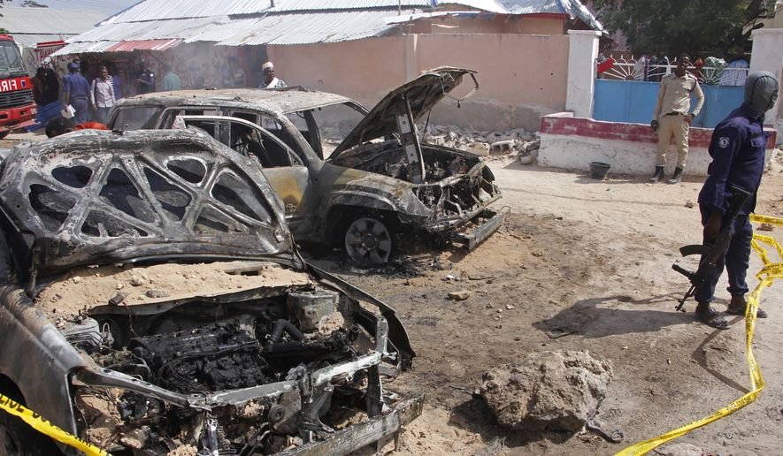 Soldiers stand near the wreckage of cars destroyed after a car bomb in Mogadishu, Somalia, Sunday, Dec. 16, 2018. At least one person was killed and others injured Sunday and nobody has claimed responsibility for the blast. (AP Photo/Farah Warsameh)