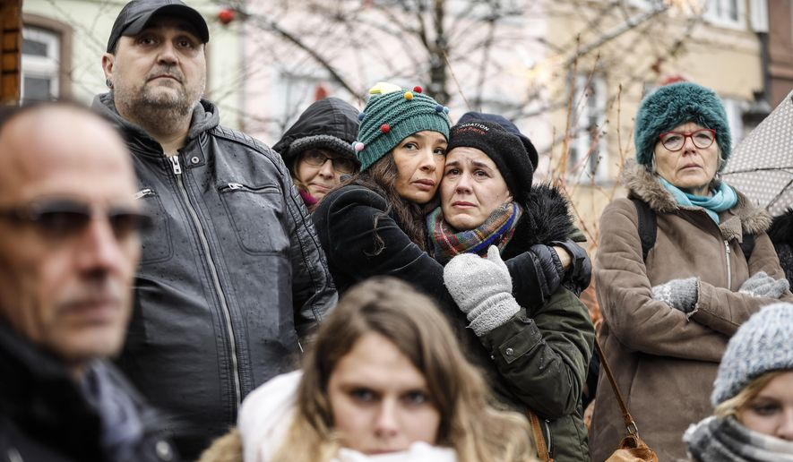 Residents react during a gathering being held in a central square of the eastern French city of Strasbourg, Sunday Dec.16, 2018 to pay homage to the victims of a gunman who killed four people and wounded a dozen more. The gathering was held in Kleber Square by a Christmas market and near where the gunman opened fire last Tuesday evening. (AP Photo/Jean-Francois Badias)