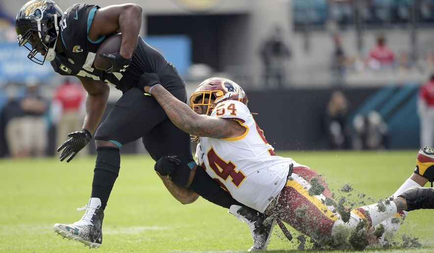 Jacksonville Jaguars running back Leonard Fournette, left, is stopped by Washington Redskins inside linebacker Mason Foster (54) after a pass reception during the first half of an NFL football game, Sunday, Dec. 16, 2018, in Jacksonville, Fla. (AP Photo/Phelan M. Ebenhack)