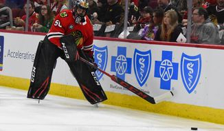 Chicago Blackhawks goaltender Corey Crawford (50) passes the puck during the first period of an NHL hockey game against the San Jose Sharks Sunday Dec. 16, 2018, in Chicago. Crawford left the game with 1:30 left in the first period after the back of his head struck the right post during a goalmouth pile-up. (AP Photo/Matt Marton)