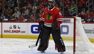 Chicago Blackhawks goaltender Corey Crawford (50) looks on during the first period of an NHL hockey game against the San Jose Sharks Sunday Dec. 16, 2018, in Chicago. Crawford left the game with 1:30 left in the first period after the back of his head struck the right post during a goalmouth pile-up. (AP Photo/Matt Marton)